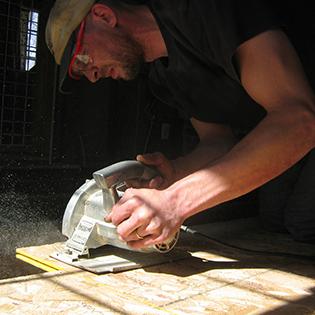 Man Cutting Plywood with a Circular Saw